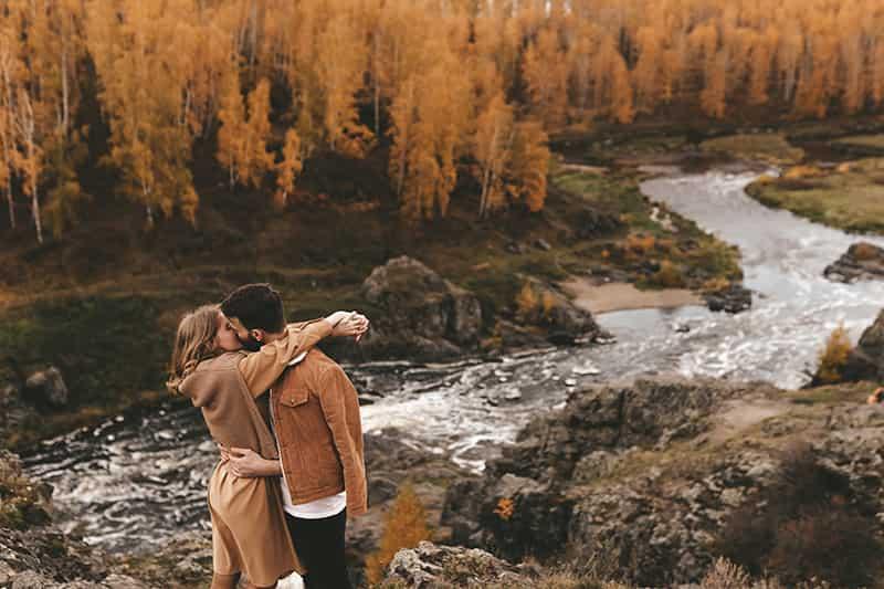 Couple s'embrassant au bord de la rivière.